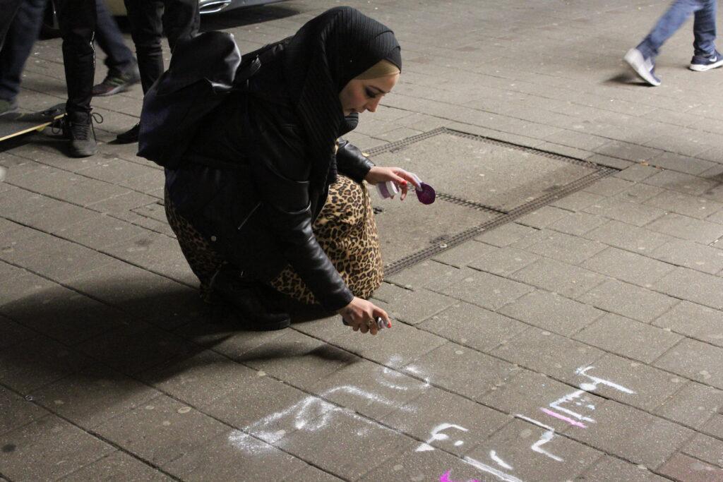 Salma sprüht Slogans auf den Steindamm. Foto: