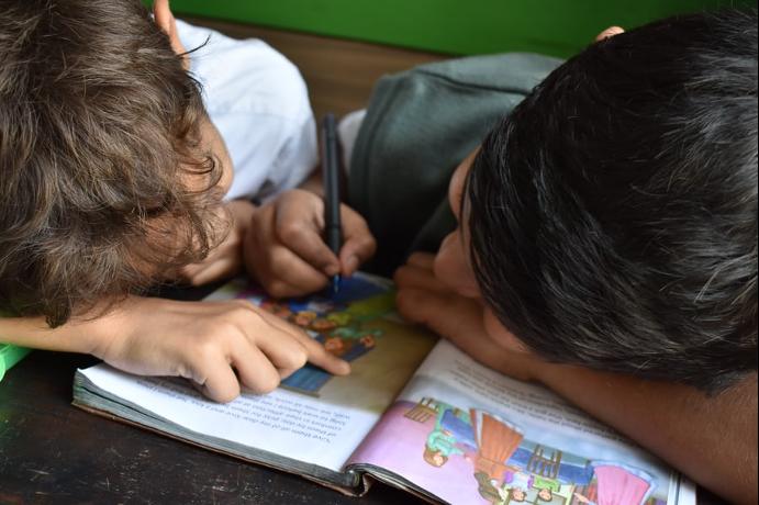 Zwei Kinder Arbeiten lehnen dicht über einer Zeitschrift, eines der Kinder schreibt oder malt mit einem Stift, das andere zeigt auf eine Textstelle, lesen lernen