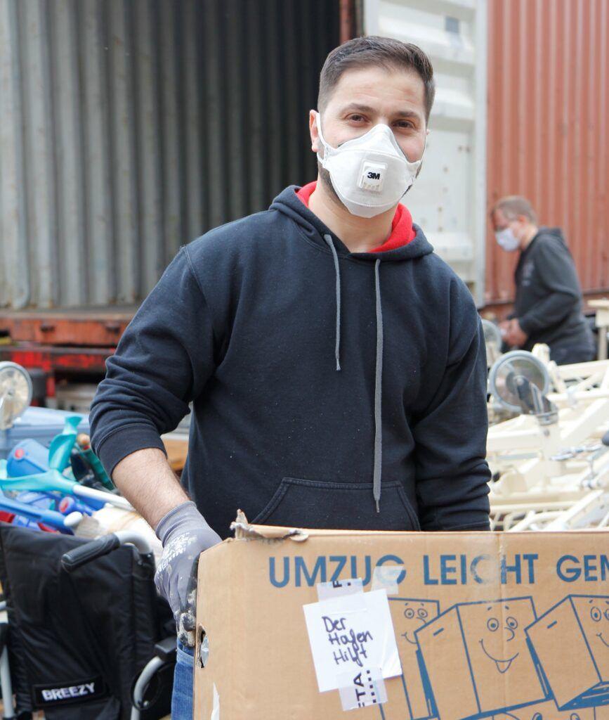 Einer der Freiwilligen trägt einen Karton mit medizinischen Utensilien in den Container