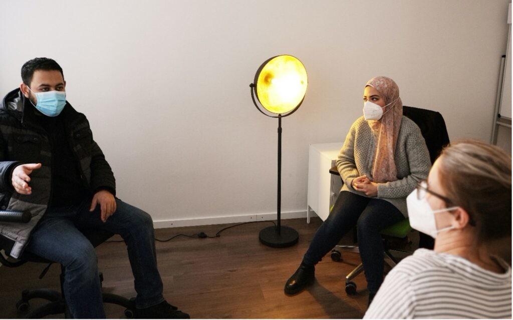Amira Mostafa übersetzt in einem Gespräch mit einem Ehrenamtlichen für MITmacher, man sieht drei Personen mit Maske, die sich unterhalten