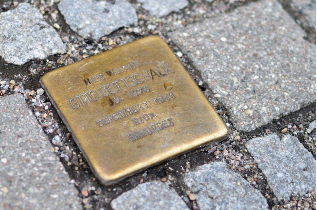 Ein Stolperstein zwischen grauen Steinen eines Bürgersteigs