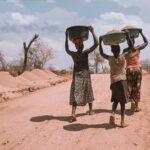 Frauen tragen Lebensmittel in einem Flüchtlingscamp in Uganda, Hungerkrise