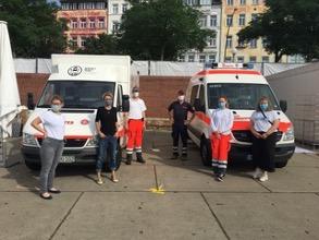 Das Women's Health Team steht vor Einsatzfahrzeugen